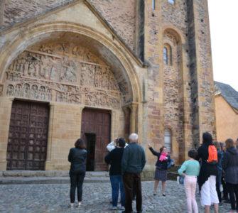 Groupe en visite guidée devant le tympan (Service Patrimoine de Conques)