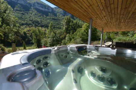 Spa sur terrasse couverte et vue rivière